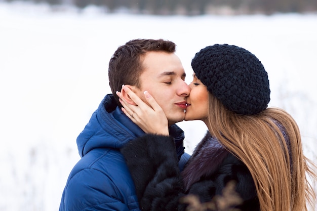 Casal jovem feliz no campo de inverno