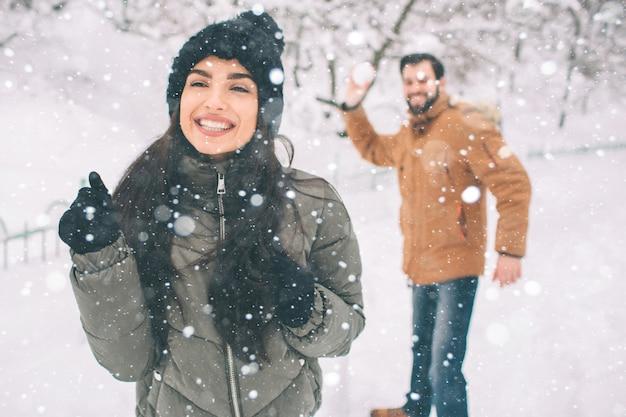 Casal jovem feliz no inverno. família ao ar livre. homem e mulher olhando para cima e rindo. amor, diversão, estação e pessoas - caminhando em winter park. ele está bola de neve