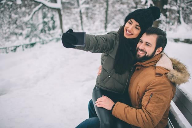 Casal jovem feliz no inverno. família ao ar livre. homem e mulher olhando para cima e rindo. amor, diversão, estação e pessoas - caminhando em winter park. eles fazem selfie