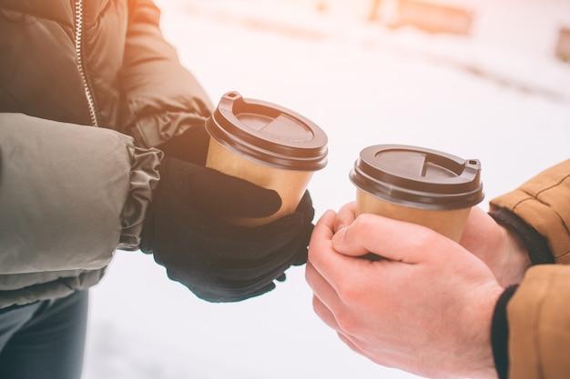 Casal jovem feliz no inverno. família ao ar livre. homem e mulher olhando para cima e rindo. amor, diversão, estação e pessoas - caminhando no parque de inverno. beber café.