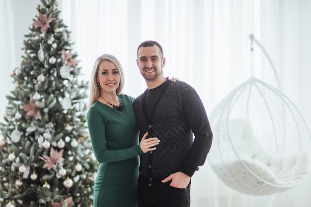 Casal jovem feliz no natal, presentes bonitos e árvore no