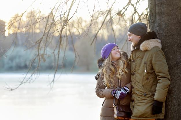Casal jovem feliz no parque de inverno
