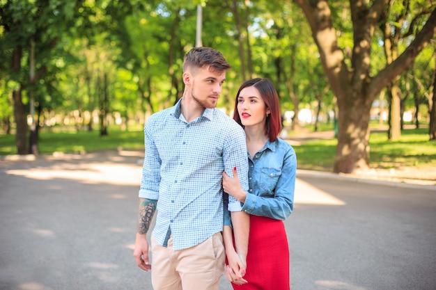 Casal jovem feliz no parque em pé e rindo no dia ensolarado