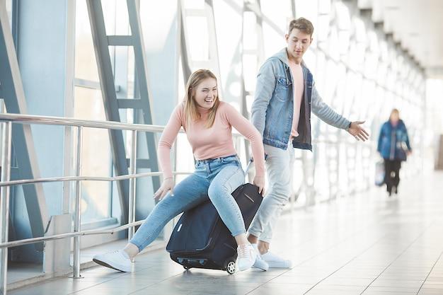 Casal jovem feliz no terminal do aeroporto se divertindo enquanto aguarda seu voo. duas pessoas homem e mulher vão tropeçar.