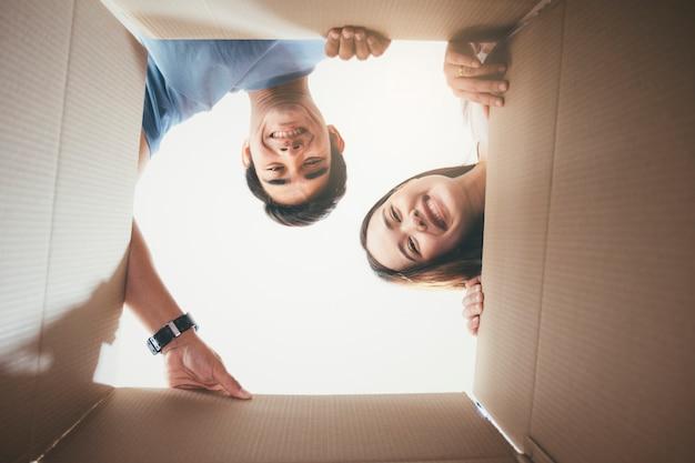 Casal jovem feliz olhando dentro da caixa