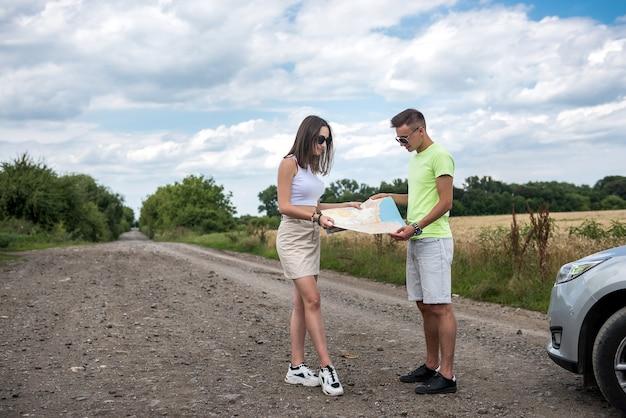 Casal jovem feliz olhando para o mapa rodoviário perto do carro. horário de verão