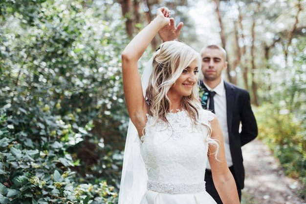 Casal jovem feliz posa para fotógrafos no seu dia mais feliz.