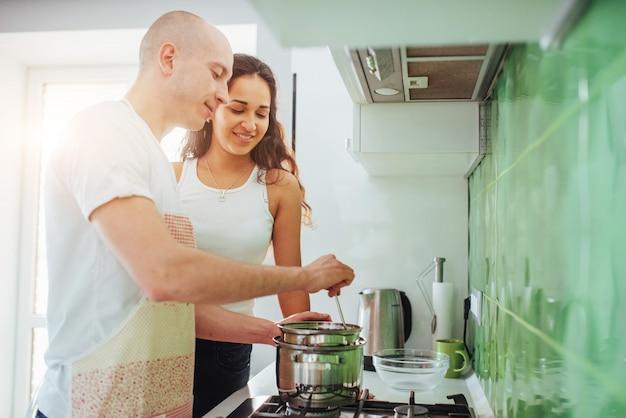 Casal jovem feliz, preparando no fogão