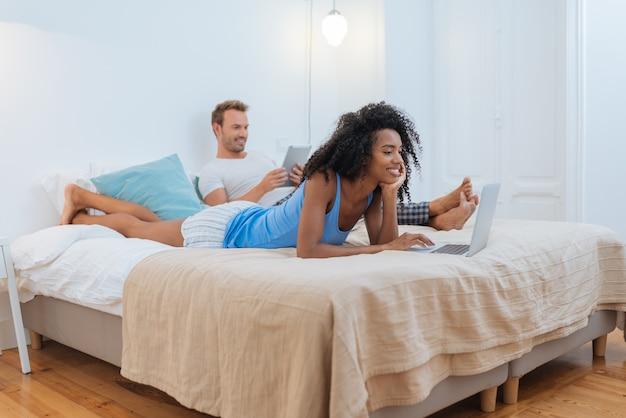 Casal jovem feliz relaxado em casa deitado na cama no tablet e computador