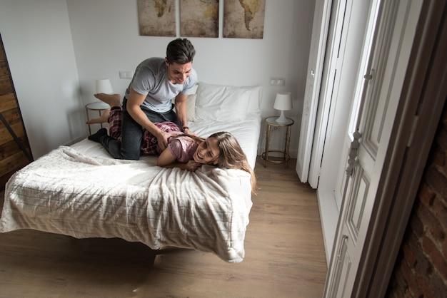 Casal jovem feliz relaxado em casa na cama