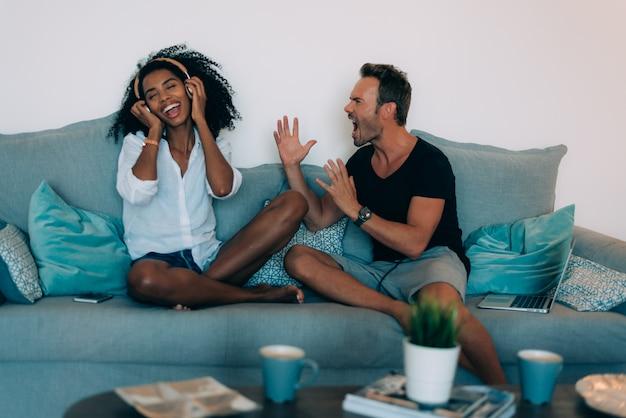 Casal jovem feliz relaxado em casa no sofá no celular ouvindo música e no computador