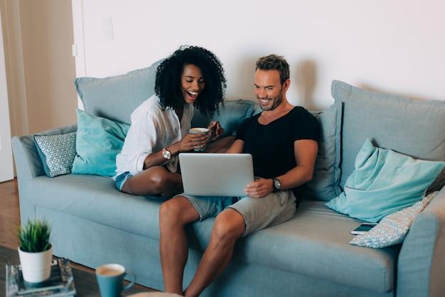 Casal jovem feliz relaxado em casa no sofá no telefone celular e computador