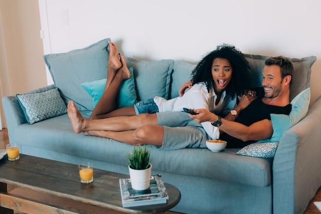 Casal jovem feliz relaxado em casa no sofá se divertindo assistindo tv