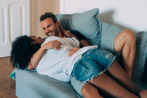 Casal jovem feliz relaxado em casa no sofá se divertindo brincando uns com os outros