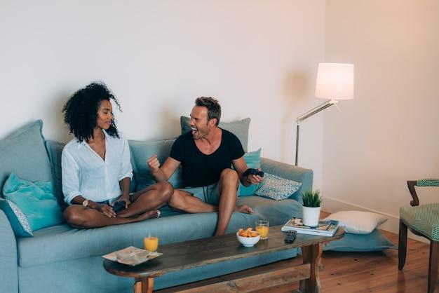 Casal jovem feliz relaxado em casa no sofá se divertindo jogando videogame