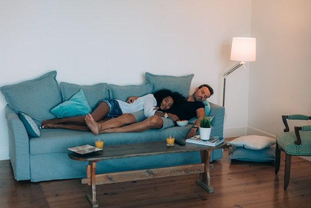 Casal jovem feliz relaxado em casa no sofá tirando uma soneca