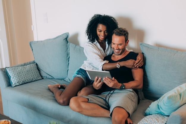 Casal jovem feliz relaxado em casa sentado no sofá sobre o tablet