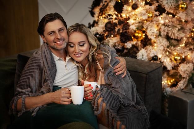 Casal jovem feliz relaxando em casa no ano novo de natal, homem sorridente e mulher se abraçando, bebendo chá