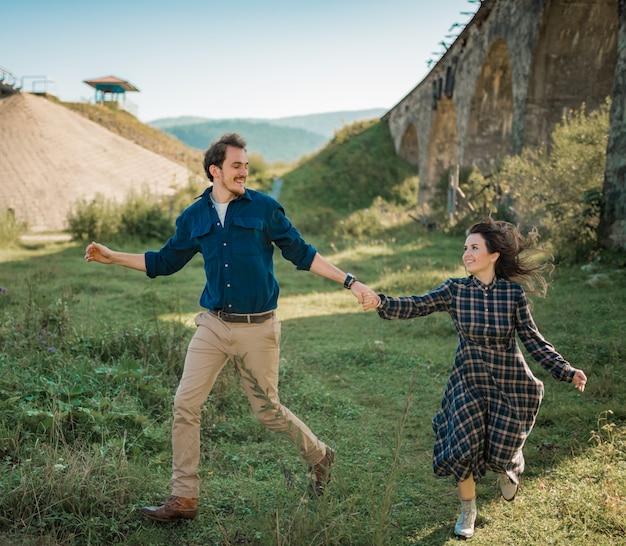 Casal jovem feliz rindo ao ar livre ao pôr do sol
