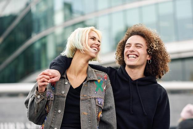 Casal jovem feliz rindo em meio urbano