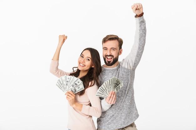 Casal jovem feliz, segurando o dinheiro faz gesto vencedor