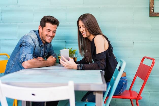Casal jovem feliz sentado em um restaurante com um smartphone