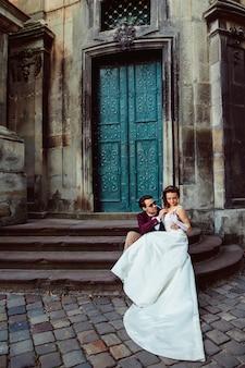 Casal jovem feliz sentado nas escadas de uma igreja antiga