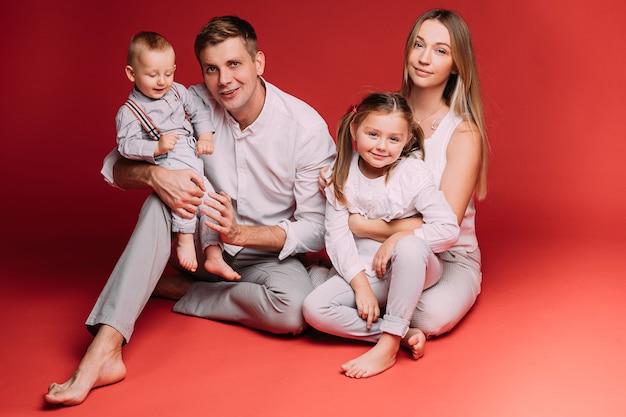 Casal jovem feliz sentado no vermelho com sua filha e um filho bebê.