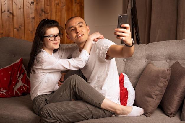Casal jovem feliz sentados juntos, olhando para o telefone. conceito romântico.