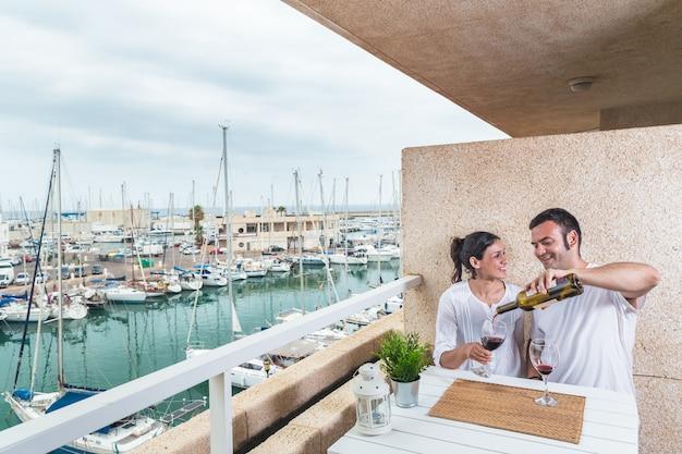 Casal jovem feliz sorrindo, bebendo vinho tinto no terraço