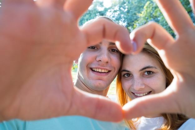 Casal jovem feliz tendo selfie ao ar livre em clima ensolarado quente.