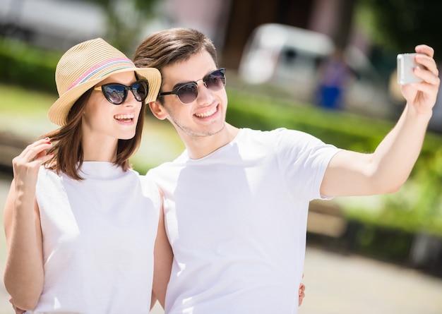 Casal jovem feliz tendo selfie no telefone ao ar livre.