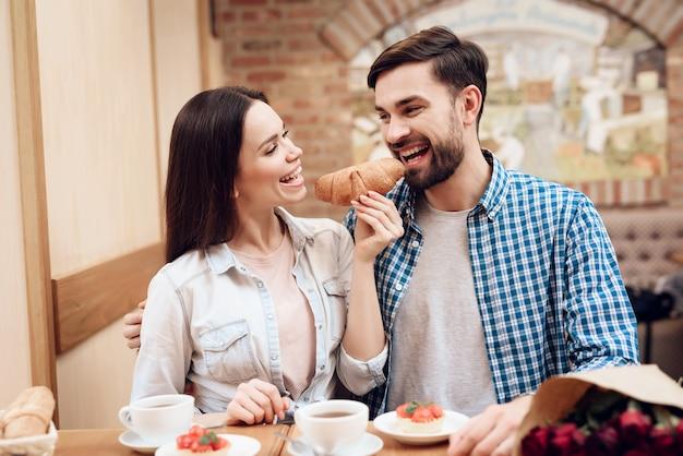 Casal jovem feliz ter data no refeitório moderno.