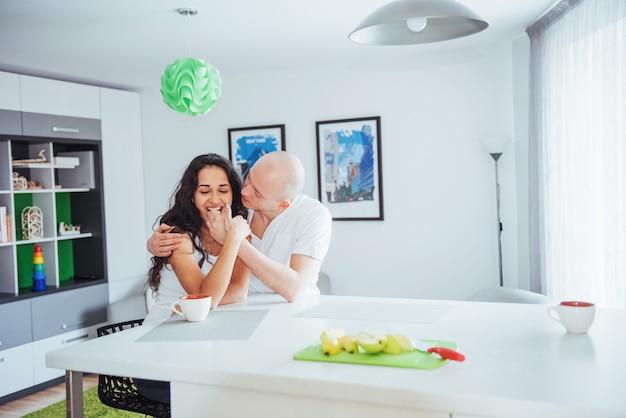 Casal jovem feliz tomando café na cozinha