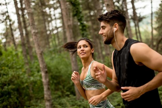 Casal jovem fitness correndo na trilha da floresta