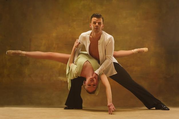 Casal jovem flexível dançando pasadoble no estúdio. retrato da moda de homem e mulher atraentes
