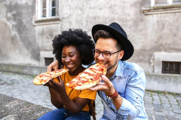 Casal jovem fofo multicultural hippie sentado ao ar livre e comendo pizza.