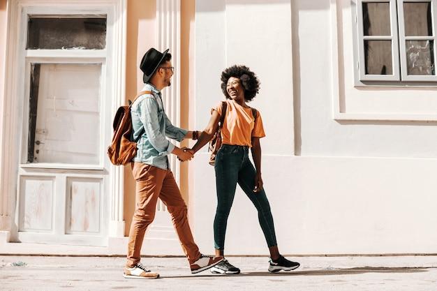 Casal jovem fofo sorridente hipster multicultural de mãos dadas e andando pela rua e se divertindo em um dia ensolarado. conceito de diversidade.