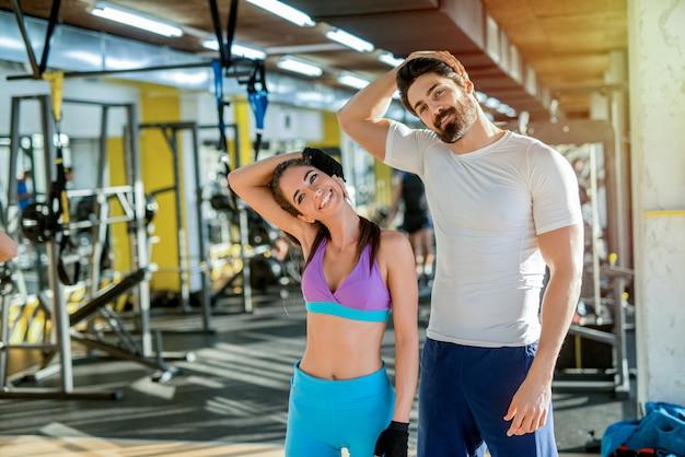 Casal jovem forte em forma, alongando os músculos após o treino no ginásio.