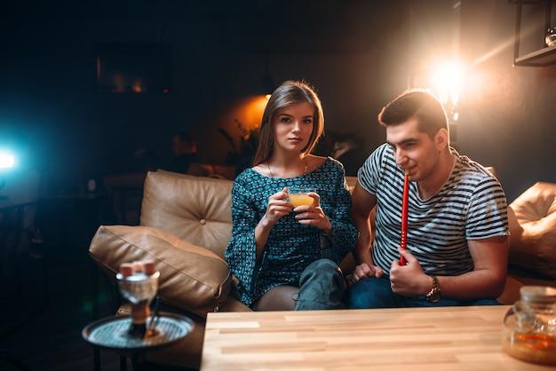 Casal jovem fumando narguilé no sofá de couro