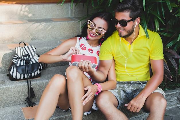Casal jovem hippie apaixonado, ouvindo música no alto-falante, sorrindo feliz, se divertindo, roupa de verão, férias tropicais, óculos de sol