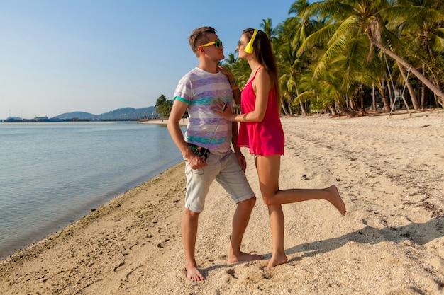 Casal jovem hippie apaixonado, praia tropical, férias, estilo moderno de verão, óculos escuros, fones de ouvido