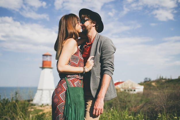 Casal jovem hippie beijando estilo indie apaixonado caminhando pelo campo, farol no fundo