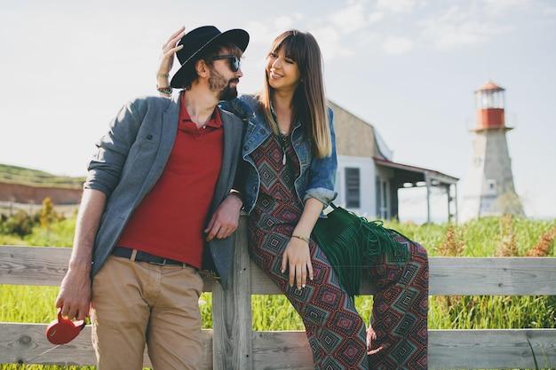 Casal jovem hippie estilo indie apaixonado caminhando pelo campo, farol no fundo, férias de verão