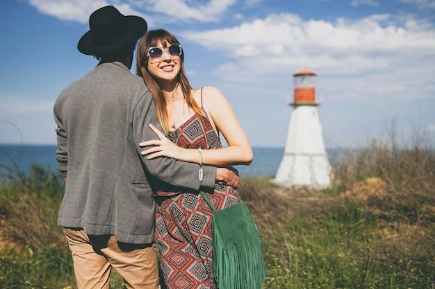 Casal jovem hippie estilo indie apaixonado caminhando pelo campo, farol no fundo