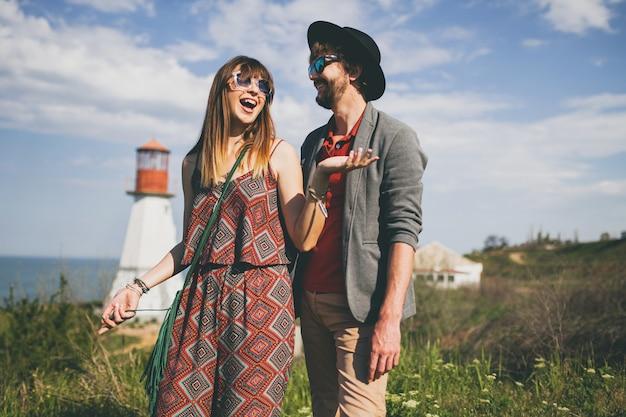 Casal jovem hippie rindo estilo indie apaixonado caminhando pelo campo, farol no fundo