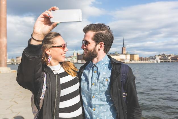Casal jovem hippie tendo um selfie em estocolmo