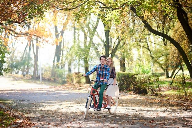 Casal jovem, homem bonito e mulher atraente na bicicleta tandem no parque ensolarado de verão ou floresta.