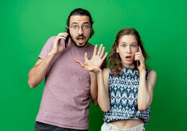Casal jovem, homem e mulher, chocados e desapontados enquanto falam em telefones celulares, em pé sobre a parede verde