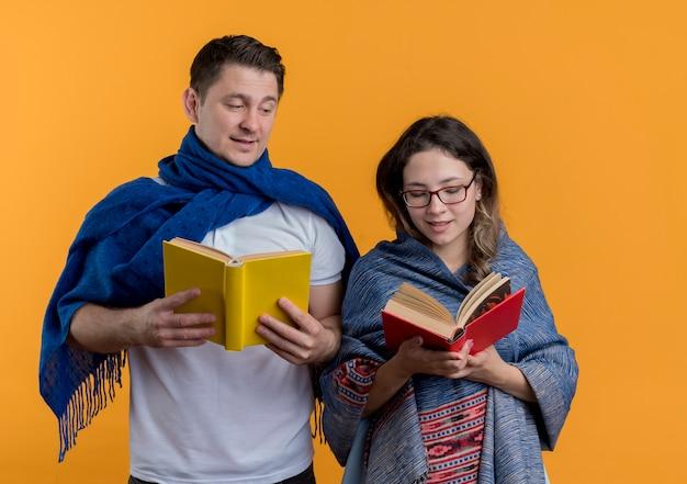 Casal jovem, homem e mulher com cobertores segurando livros, feliz e positivo, sorrindo em pé sobre uma parede laranja